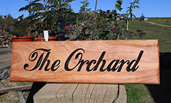 "macrocarpa sign 500 x 140 ""the orchard"" with plants in the background"