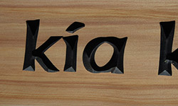 kia carved text close up on macrocarpa