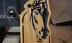 number carved into pine with horse head carved at top for horse farm