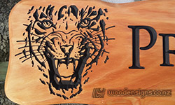 tiger face carved into macrocarpa wood